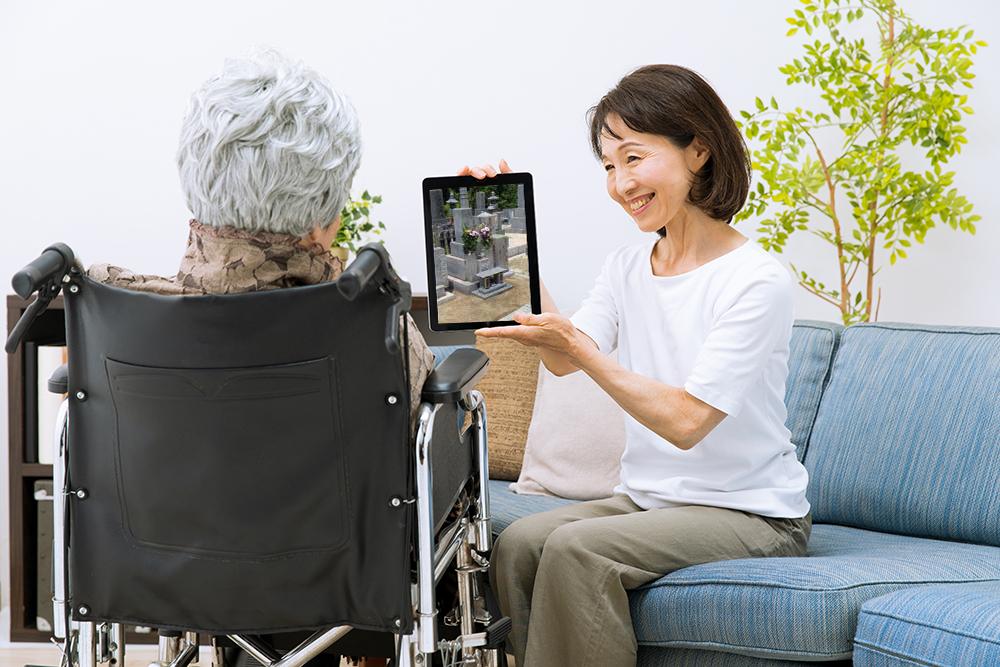 おばあさんがipadでオンラインお墓参りを見ている様子